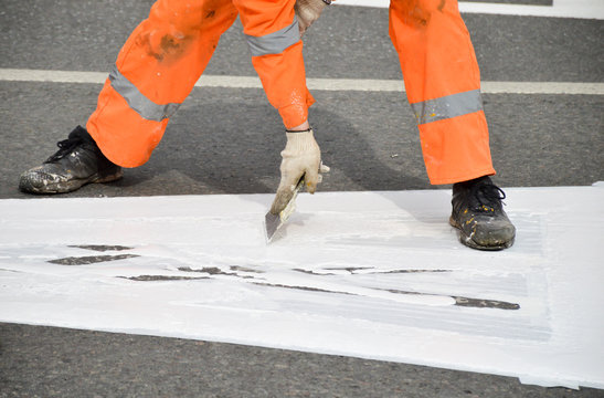 Road worker makes white paint