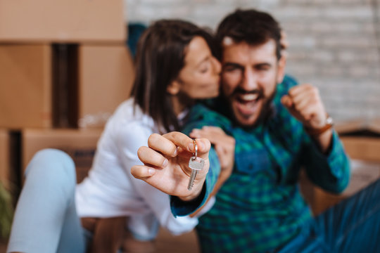 Young happy couple showing the keys of a new home