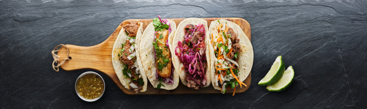 four mexican street tacos with fish barbacoa and carnitas shot in panoramic composition on top of serving wooden board