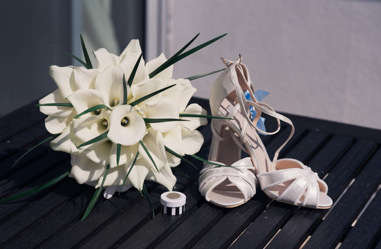 Wedding shoes, bouquet and lucky sixpence