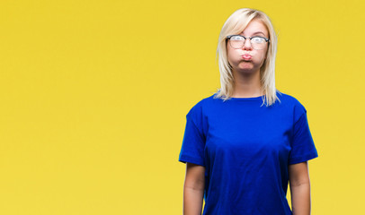 Young beautiful blonde woman wearing glasses over isolated background puffing cheeks with funny face. Mouth inflated with air, crazy expression.