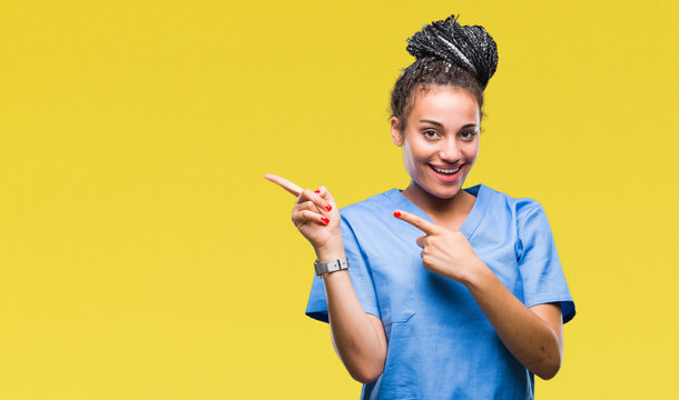 Young braided hair african american girl professional nurse over isolated background smiling and looking at the camera pointing with two hands and fingers to the side.