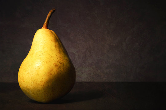 Pear on dark grunge background. Still life with juicy pear