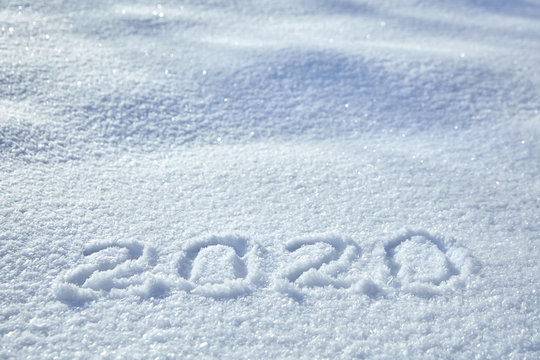 Numbers, calendar date, inscription 2020 on natural snowy surface in wintertime. Text, Winter New Year holiday background