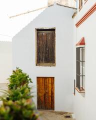 wooden doors on white wall in european village in spain