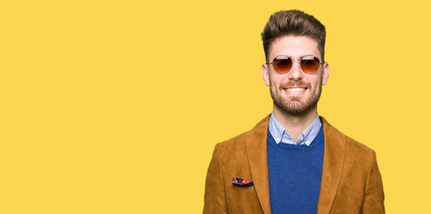 Young handsome elegant man wearing sunglasses with a happy and cool smile on face. Lucky person. Wall mural
