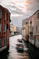 two boats drive down the canal in venice italy