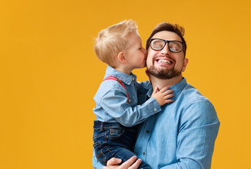 happy father's day! cute dad and son hugging on yellow background.