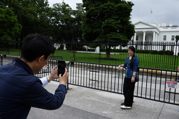 A man takes a picture of a woman on his phone outside the White House in Washington