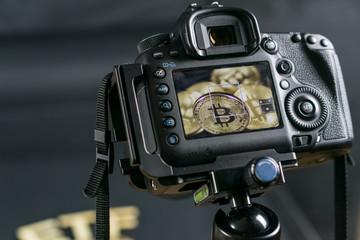 DSLR camera taking a macro photo of Bitcoin coins. Bitcoin under eye of goverment concept