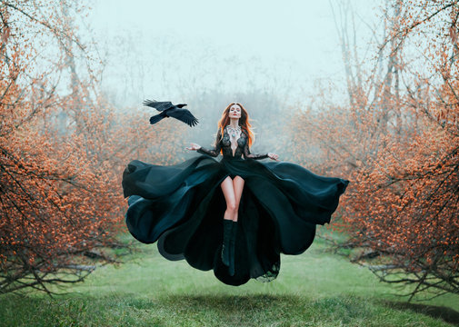 girl with bright red hair levitates above ground, powerful sorceress, forest goddess in black flying dress with lace on open chest and bare long legs, lady in flowering orange garden and hand raven