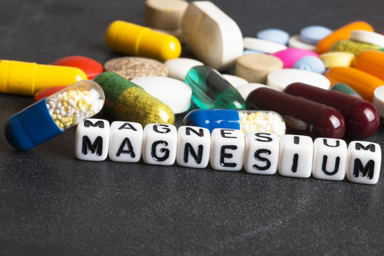 Magnesium mineral food supplement written with plastic letters on dark background