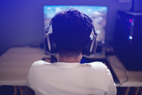 Portrait of asian boy gamer playing games on computer in the room at home