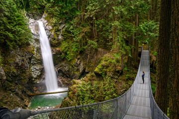 Woman standing on a suspension bridge and looking at the Cascade falls, in Cascade falls regional park, Deroche, British Columbia, Canada Wall mural