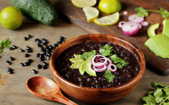 black bean soup or stew. Latin American or Mexican cuisine. stewed black beans served with avocado and red onion and cilantro.