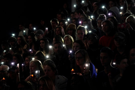 People hold up the phone lights during a moment of silence at a vigil for the victims of the shooting at the Science, Technology, Engineering and Math (STEM) School in Highlands Ranch