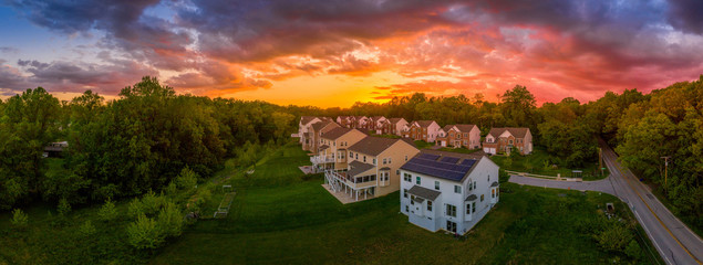 Modern American upper middle class single family homes neighborhood street with brick facade with solar panel in Columbia Maryland USA during sunset