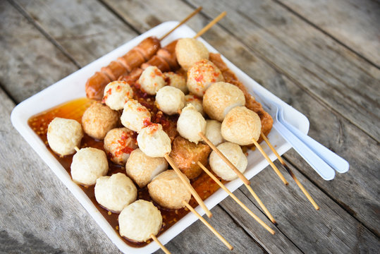 Meat ball , fish ball and sausage hotdog grilled in stick on tray with wooden background Thai style food