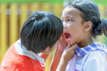 Asian Little girl see teeth in the mouth her friend.