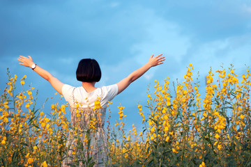 Backside of  Asian young woman enjoy and stretching her arms with sky background in nature yellow flower farm, her is feeling relaxed and happy in the sunset; Relax and happy concept.