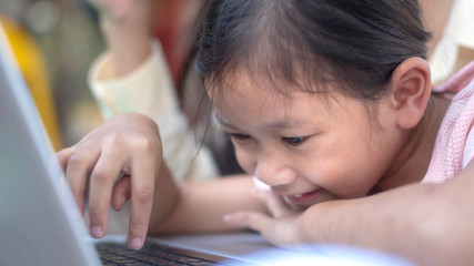 Preschool child playing computer; The little girl play laptop in the living room at home, happy loving family.The concept strengthens the imagination of children.