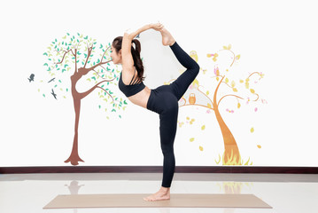 healthy women practicing yoga in gym . standing stretching in Natarajasana pose,concept for exercising and health care indoor.
