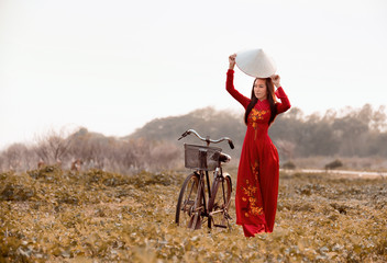 Vietnamese Beautiful woman with traditional dress (ao dai) and conical hat in Ho Chi Minh Vietnam wilderness walk
