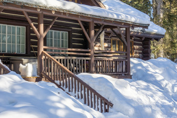 wooden house covered in snow in the early spring woods alberta canada.