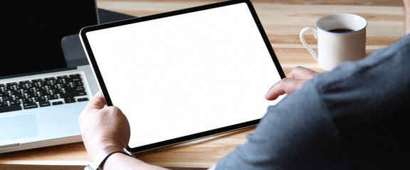 Closes up man holding tablet with isolate white screen on home office workspace