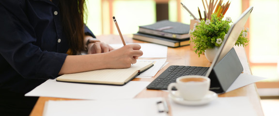 Cropped shot of woman freelancer writing on notebook on table in office