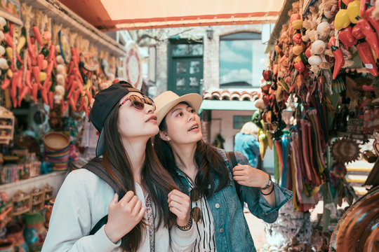 two asian young women on summer vacation walking in outdoor mexican  market. smiling friends ladies shopping in local vendor selling decor chilli for home in olvera street. girls look up together.