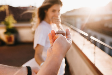 Man holding wedding ring in front of astonished happy girl covering mouth with hand. Romantic photo of charming woman standing on roof early in evening on date with boyfriend in anniversary.