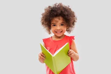 childhood, literature and people concept - happy little african american girl reading book over grey background