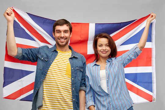 patriotism and national concept - happy couple holding british flag over grey background