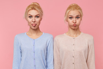 Photo of beautiful young blonde twins make faces, show tongue and blow cheeks, looking at the camera isolated over pink background.