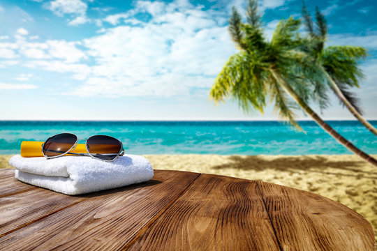 Wooden table background of free space for your decoration. White towel background with sunglasses and beach landcsape with palms and ocean. Blue sky with sun light. Summer time on beach.
