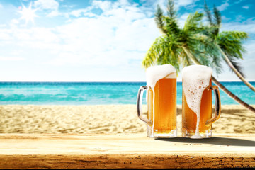 Summer background of wooden desk and cold beer. Free space for your decoration. Beach landscape with palms and ocean. Summer sunny day with sun light. Beach party and summer time.