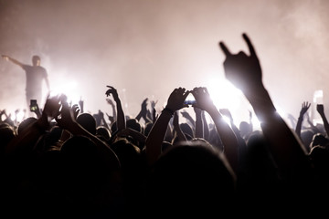 Crowd with raised hands and smartphone record a concert.