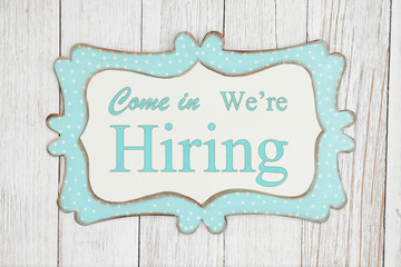 Come in we're hiring text on a retro tin polka dot picture sign