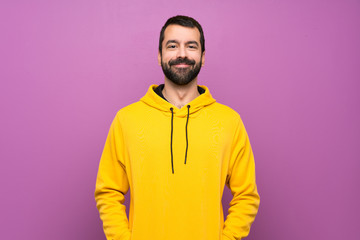 Handsome man with yellow sweatshirt laughing Wall mural