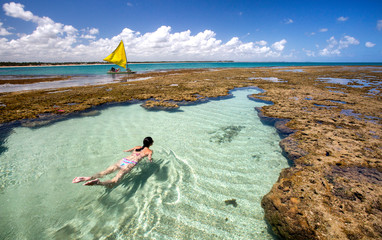 Woman swimming and relaxing on natural pool in Porto de Galinhas, Pernambuco - Brazil. Brazilian beach