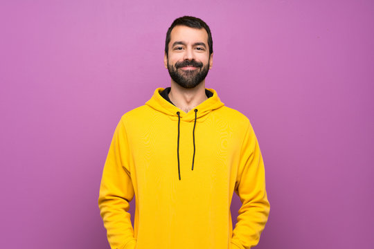 Handsome man with yellow sweatshirt laughing
