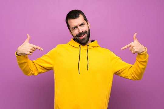 Handsome man with yellow sweatshirt proud and self-satisfied