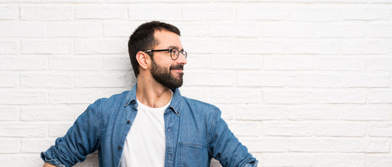 Handsome man with beard over white brick wall posing with arms at hip and smiling