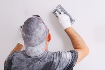Plasterer polishing a gypsum wall. House renovation concept.