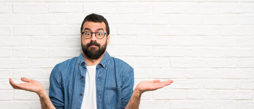 Handsome man with beard over white brick wall having doubts while raising hands
