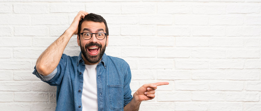 Handsome man with beard over white brick wall surprised and pointing finger to the side