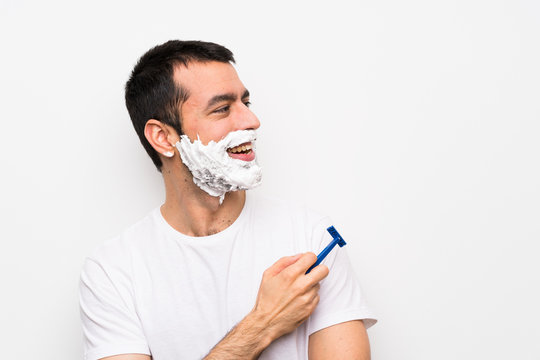 Man shaving his beard over isolated white background looking to the side