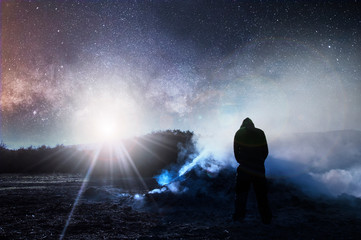 A science fiction night time edit. With a hooded figure looking at a bonfire and smoke with the sky full of stars and a bright light in the sky.