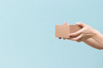 Woman hand hold the brown corrugated box on blue  wall background with copy space